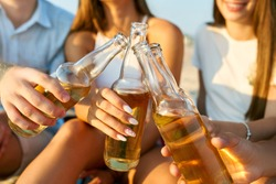 Group of friends having fun enjoying refreshing beverage and relaxing on the beach at sunset. Young men and women drink beer sitting on a sand in the warm summer evening. Isolated view of bottles.