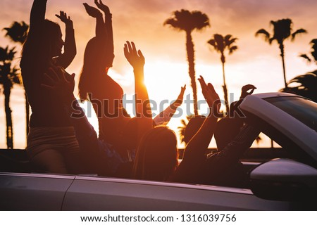 Group of friends having fun in convertible car during road trip at sunset - Young travel people driving a cabriolet during summer holidays - Happiness, vacation and youth lifestyle concept