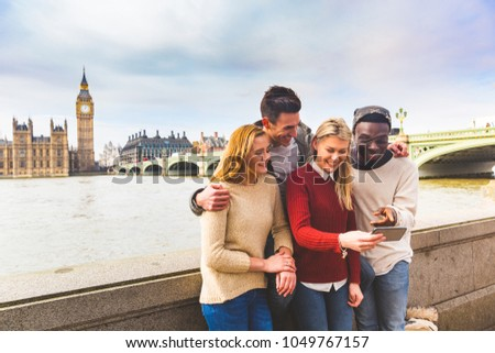 Group of friends having fun in London and looking at a smartphone. Mixed race people laughing and enjoying their time in the city. Big ben and Westminster parliament on background.