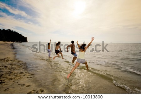 group of friends having fun jumping into the sea on sunset