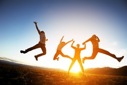 Group of friends having fun jumps on sunset and mountains backdrop