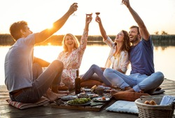 Group of friends having fun on picnic near a lake, sitting on pier eating and drinking wine.