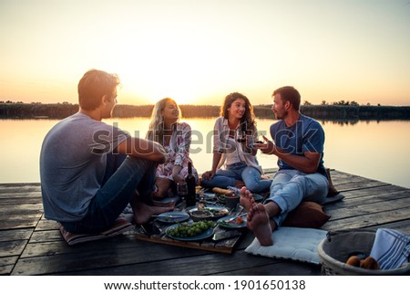 Group of friends having fun on picnic near a lake, sitting on pier eating and drinking wine. Stock photo ©