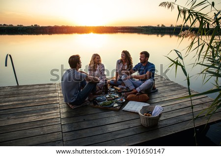 Group of friends having fun on picnic near a lake, sitting on pier eating and drinking wine. Foto d'archivio ©