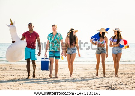 Group of friends having fun on the beach - Young and happy tourists bonding outdoors, enjoying summertime