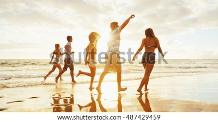 Stock Photo Group of friends having fun running down the beach at sunset