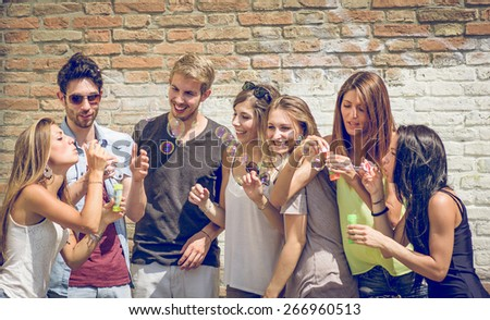 group of friends having fun together and making soap bubbles. concept about friendship and people
