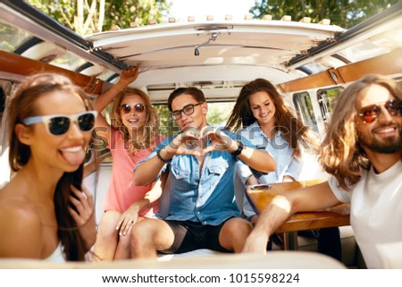 Group Of Friends Having Fun, Traveling In Car In Summer. Happy Smiling Young People In Stylish Clothes Sitting In Retro Bus While Having Trip On Summer Vacation. Summertime. High Resolution.