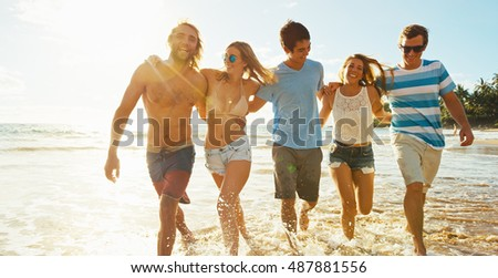 Stock Photo Group of friends having fun walking down the beach at sunset