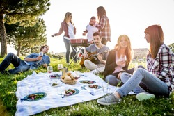 Group of friends having fun while eating and drinking at a pic-nic - Happy people at bbq party