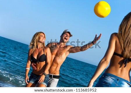 Group of friends having fun with inflatable ball on beach.