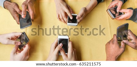 Group of friends having fun with smartphones - Closeup of hands social networking with mobile cellphones - Wifi connected people in bar - Technology concept - Main focus on center hands