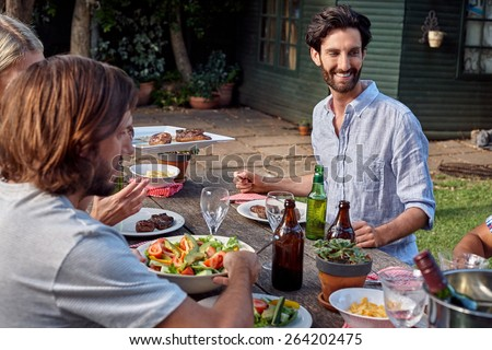 group of friends having outdoor garden barbecue salad dinner with drinks