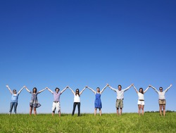 Group of friends holding hands in meadow under blue sky