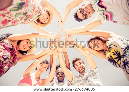 Group of friends in circle looking down and rising hands - Several people exulting on the beach at sunset - Concepts about summer,lifestyle and happiness