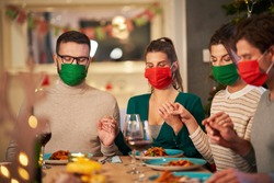 Group of friends in masks praying over Christmas Thanksgiving table at home
