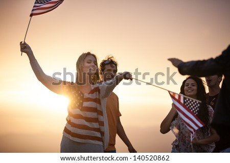 Group of Friends in their twenties dancing on the Beach at Sunset in California