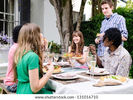 Group Of Friends Interacting At An Outdoor Garden Party ...