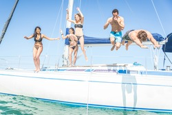 Group of friends jumping from the boat. having fun on the yacht and in the water. hot summer day and private boat party