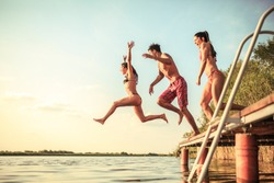 Group of friends jumping into the lake from wooden pier. Summer day fun.