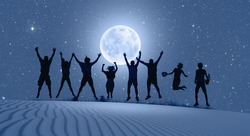 Group of friends jumping on top of dune with arms raised in air with full blue moon