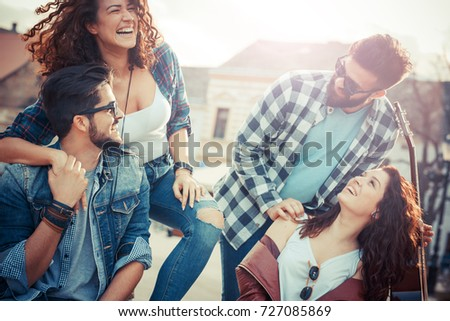 Group of friends laughing and walking at the city downtown.They embrace each other and smiling.