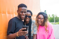 group of friends laughing over something they're viewing on a mobile phone. friends laughing together