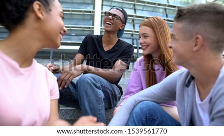 Group of friends laughing sitting school stairs after lessons, teen friendship #1539561770