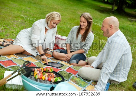 Group of friends looking at pictures outdoors in park