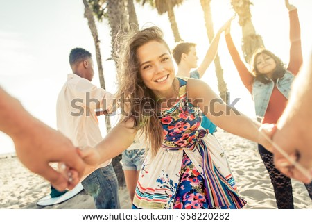 Group of friends making beach party. Young beautiful woman pulling and inviting her into the group