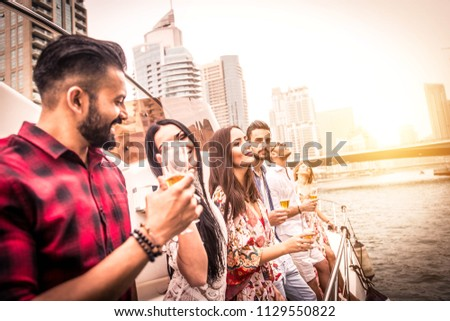 Group of friends making party on a yacht in Dubai - Happy people having a fancy party on a luxury boat #1129550822