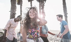 Group of friends making party on the beach and dancing together