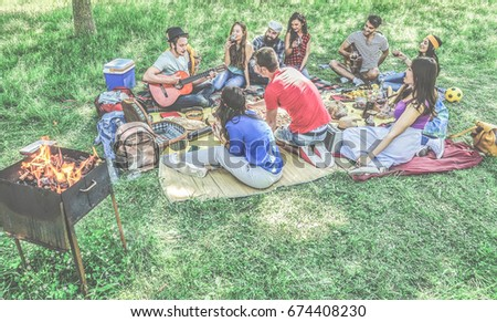 Group of friends making picnic barbecue outdoor in city park - Young people having fun playing music and relaxing at bbq party sitting on grass - Main focus on bottom guys - Contrast filter
