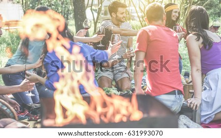 Group of friends making picnic with barbecue on city park outdoor - Young people eating bbq meal and drinking wine at dinner in backyard - Focus on behind right guys - Youth concept - Vintage filter