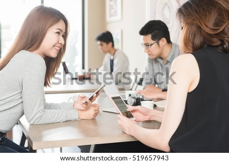 Group of friends meeting in a coffee shop chatting to each other while using smartphone tablet and laptop, internet of things conceptual #519657943