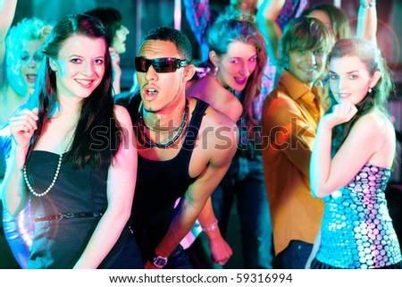 Group of friends - men and women of different ethnicity - dancing to the music in a disco club having lots of fun