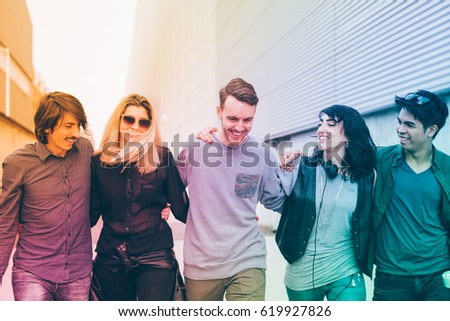 Group of friends multiethnic millenials walking arm aroung outdoor having fun - togetherness, happiness, friendship concept - filtered colorful