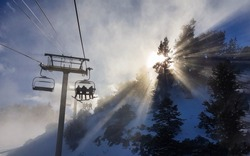 Group of friends on a snowboarding trip to Copper Mountain ride the chairlift through the fog on sunny winter morning. Morning sunbeams shine on snowboarders riding ski lift up to the top of mountain.