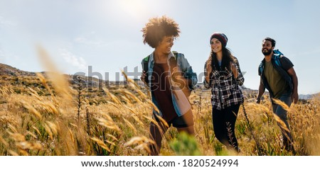 Group of friends on country walk. Young people hiking in countryside.