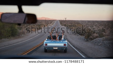 Group Of Friends On Road Trip Driving Classic Convertible Car Viewed Through Windshield Of Following Vehicle #1178488171