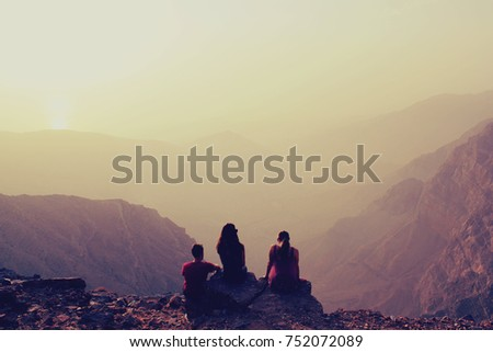 Group of friends on sunset at the top of the mountain, sky background, United Arab Emirates