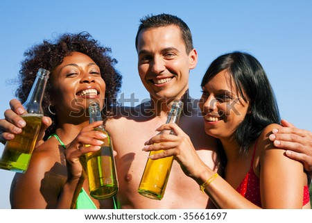 Group of friends - one man hugs two women and all have drinks in swimwear