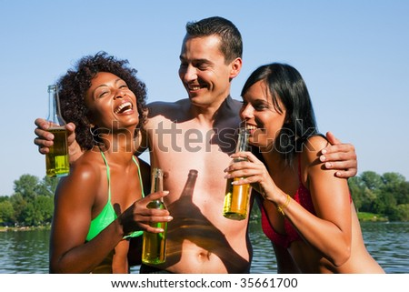 Group of friends - one man hugs two women and all have drinks in swimwear on the beach of a lake in summer