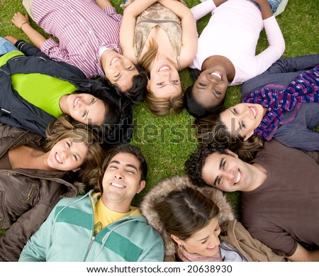 group of friends or college students outdoors with heads together