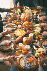 Group of friends or family members giving thanks to God at festive turkey dinner table together. Thanksgiving celebration traditional dinner concept