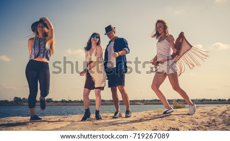 Group of friends partying and dancing at the beach, positive mood