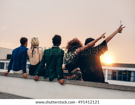 Group of friends partying on terrace with drinks. Young men and women enjoying drinks on rooftop at sunset. #491412121