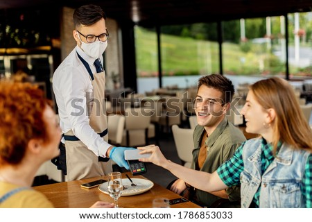 Group of friends paying contactless with mobile phone to a waiter in a cafe. Focus is on waiter.