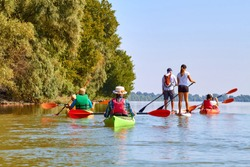 Group of friends (people) travel by kayaks. Kayaking in wilderness of Danube river in summer. Peacefull nature scene of calm river. Water tourism concept.