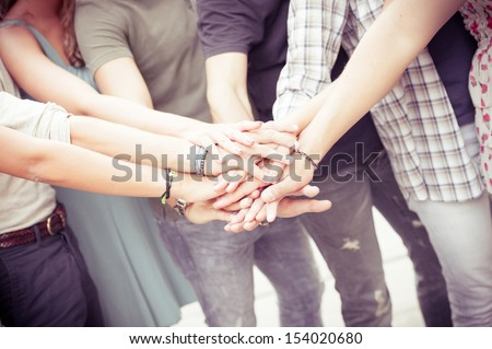 Group of friends pile up hands as unity oath,Italy
